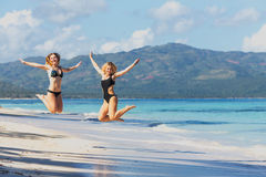 Two girls jumping on the beach royalty free stock photography
