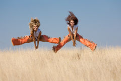 Two girls jumping at the field Stock Image