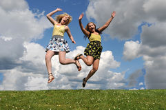 Two girls jumping in grass field Stock Photos