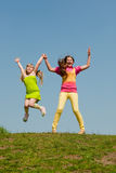 Two girls jumping on green meadow Royalty Free Stock Images