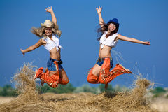 Two girls jumping on haystack Stock Photos