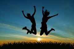 Two girls jumping for joy at sunset stock photo