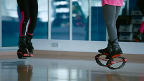 Two girls jumping in kangoo shoes in the dance studio stock footage