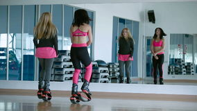 Two girls jumping with kangoo shoes in the dance studio stock footage