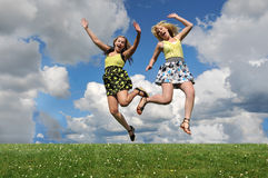 Two girls jumping over grass hill royalty free stock images