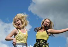 Two girls jumping in the sky Royalty Free Stock Photography