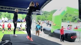 Two girls jumping on stage and showing aerobic exercises stock footage