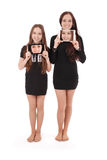 Two girls keeps tablet pc in front of yourself Royalty Free Stock Images