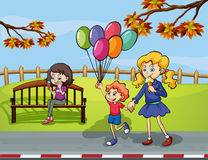 Two girls with a kid holding a balloon in the park Royalty Free Stock Image