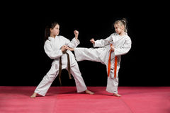 Two girls in kimono are training paired exercises karate.  Stock Photo