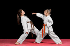 Two girls in kimono are training paired exercises karate.  Stock Photography