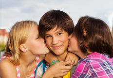 Two girls kiss boy in cheeks close up view. Two girls kissing smiling cute boy in cheeks in close up view Stock Images