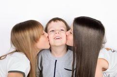 Two girls kissing boy. On the light background, horizontal Royalty Free Stock Photography