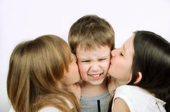 Two girls kissing little angry boy on the light background Royalty Free Stock Image