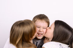 Two girls kissing little laughing boy Royalty Free Stock Images