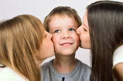 Two girls kissing little smiling boy Royalty Free Stock Photo