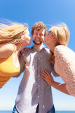 Two girls kissing one boy having fun outdoor Stock Photos
