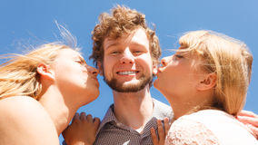Two girls kissing one boy having fun outdoor Stock Images