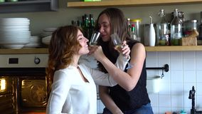 Two girls in the kitchen drink champagne and laugh. Two young female drink champagne and laugh at home with happy faces stock video