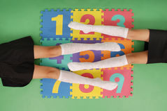 Two girls in knee-length socks on rug with numbers Royalty Free Stock Photos