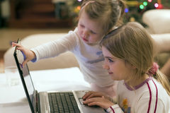Two girls and laptop computer. Two little girls sitting in front of a laptop computer, both very attracted to the screen. One touching the screen Royalty Free Stock Image