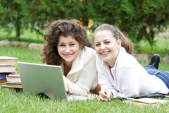 Two girls with laptop on nature Stock Photos