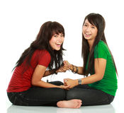 Two girls laughing. Portrait of attractive two girls laughing to the camera on white background Royalty Free Stock Image