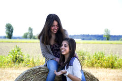 Two girls laughing in a field Royalty Free Stock Image