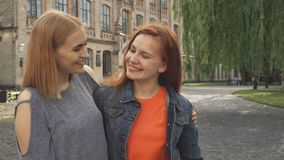 Two girls laughing and hugging. Women smiling and hugging. They look aside, then at each other and at camera. Girls standing outdoors near university stock footage