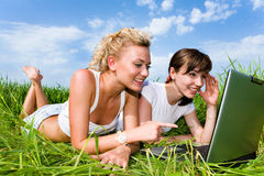 Two girls laughing and looking at laptop computer. Two beautiful girls in white clothes are laughing and looking at laptop computer outdoors. Lay on the green Stock Photo