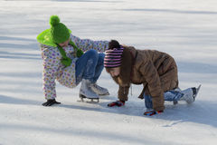 Two girls laughing rising after falling on ice royalty free stock images