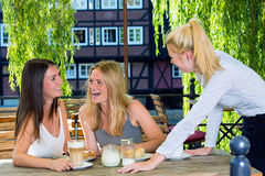 Two girls laughing talking to female waiter Stock Photography