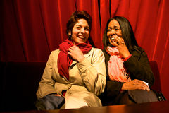 Two girls laughing at the theatre with a red curtain in the back Stock Photos