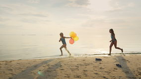 Two girls laughing together. Playing on the beach, catching up with each other. Holding balloons stock video footage