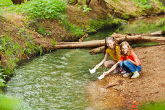 Two girls launching paper boats from riverside Royalty Free Stock Photography