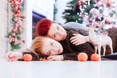 Two girls lay on the floor. Two girls lay on the wooden floor in front of Xmas tree Stock Image