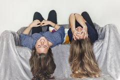 Two girls laying upside down on a grey sofa at home smiling Stock Image