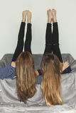 Two girls laying upside down on a grey sofa with legs up Royalty Free Stock Photography