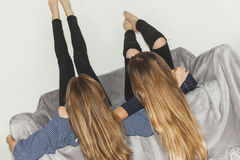 Two girls laying upside down on a grey sofa with legs up Royalty Free Stock Photos