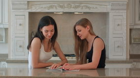 Two girls leaf through a magazine on the kitchen. People stock footage