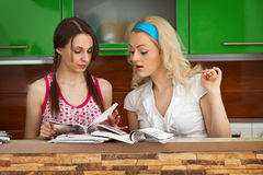 Two girls leaf through  magazines on kitchen Royalty Free Stock Image