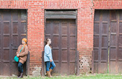 Two Girls leaning on Brick Wall Stock Image