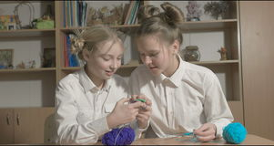 Two girls learn to knit in the classroom or room stock footage
