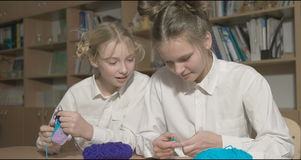 Two girls learn to knit in the classroom or room stock video