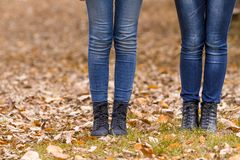 Two girls legs in boots on autumn leaves. Girls feet boots walking on fall leaves outdoor with autumn season nature on background Royalty Free Stock Photo