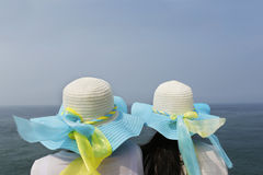 Two Girls for leisure by the sea. Two Girls in hat sit by the sea Stock Images