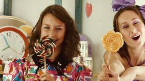 Two girls lick candies and show them in the camera stock footage