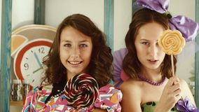 Two girls lick candies and show them in the camera stock video footage