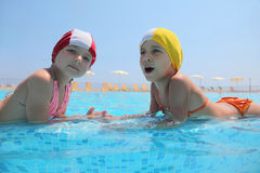 Two girls lie in day-time in pool and speak Stock Photography