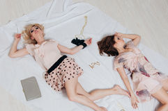 Two girls lie on the floor among accessories Royalty Free Stock Photography